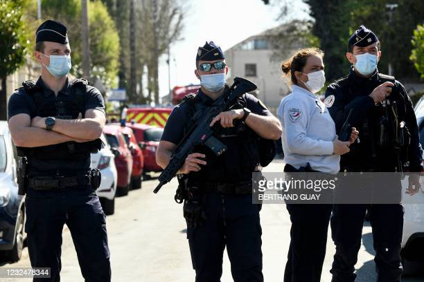 French police officials block off a street near the police station in Rambouillet, south-west of Paris, on April 23 after a woman was stabbed to...