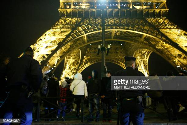 French police patrol in front of the Eiffel Tower in Paris on New Year's Eve December 31 2015 / AFP PHOTO / MATTHIEU ALEXANDRE