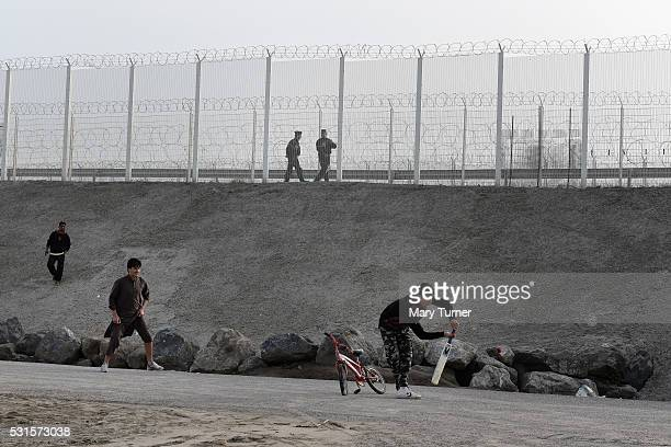 French police patrol the borders of the port of Calais as young refugees and migrants from Afghanistan play a heated game of cricket in the 'Jungle'...