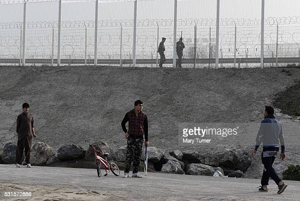 French police patrol the fenced off borders of the port of Calais as young refugees and migrants from Afghanistan play a heated game of cricket in...