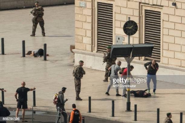 TOPSHOT French police point a gun at a man on the ground as a stabbed woman lies while soldiers secure the area following an attack on October 1 2017...