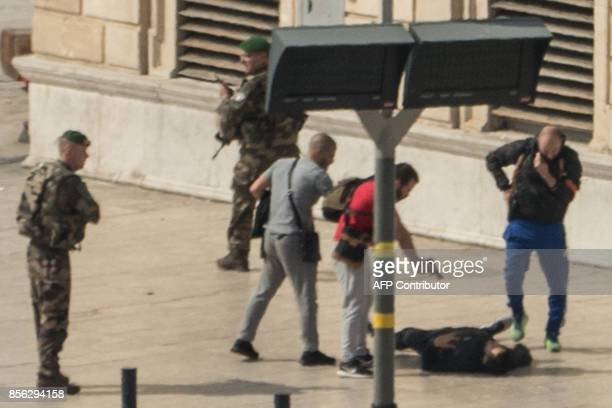 French police point a gun at a man on the ground while soldiers secure the area following an attack on October 1 2017 at the SaintCharles main train...
