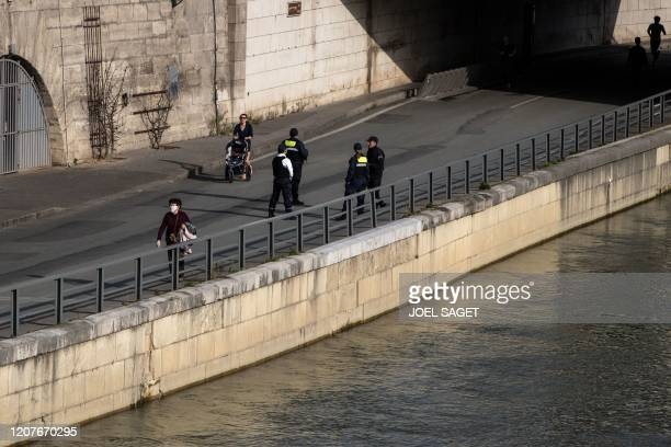 French police stand along the quay of the River Seine as joggers and walkers pass by on March 19, 2020 in central Paris, as a strict lockdown comes...