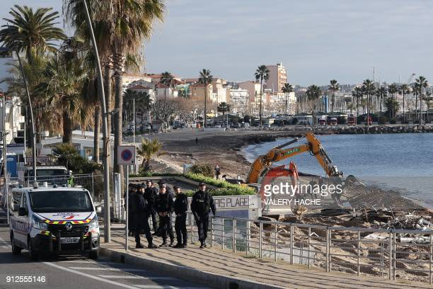 French police stand by as an excavator is used to demolish three restaurants on Vallauris Beach in GolfeJuan southeastern France on January 31 2018...