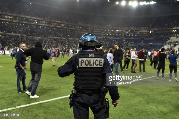French police stand guard after clashes between supporters before the UEFA Europa League first leg quarter final football match between Lyon and...