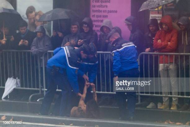 French police tackle a FEMEN protester after she approached the motorcade of the US President as he arrives to participate in the Armistice Day...