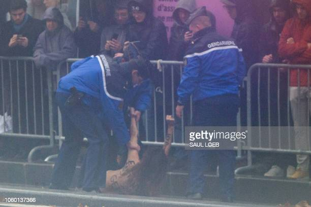 TOPSHOT French police tackle a FEMEN protester after she approached the motorcade of the US President as he arrives to participate in the Armistice...