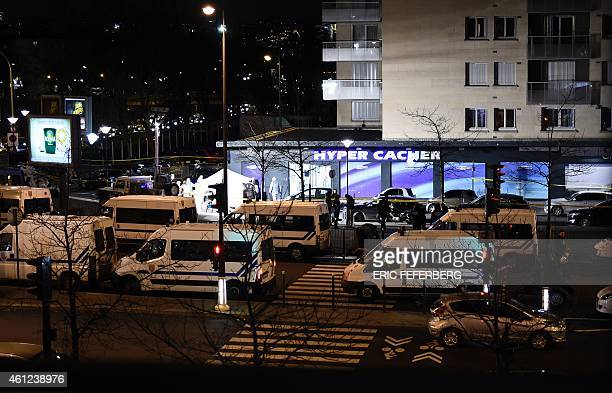 French police vehicles take position outside the Hyper Cacher kosher grocery store near Porte de Vincennes in eastern Paris on January 9 2015 after...