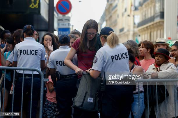 A French police woman check a bag of a visitor as she arrives to watch the annual Bastille Day military parade on the ChampsElysees avenue in Paris...