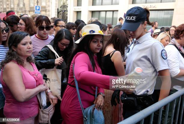 A French police woman checks visitors as they arrive to watch the annual Bastille Day military parade on the ChampsElysees avenue in Paris on July 14...