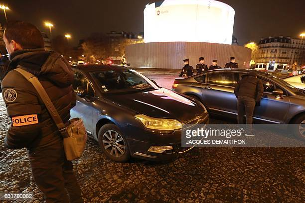 A French policeman and French antiriot police officers stand guard by VTC drivers as they block part of Place de la Bastille in Paris on January 16...