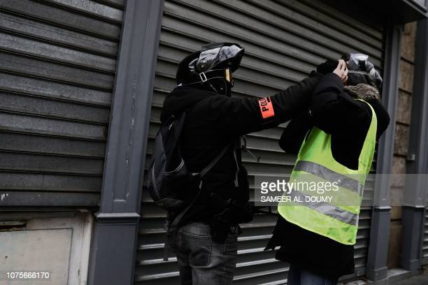 French policeman clashes with a protestor during a demonstration called by the yellow vests movement to protest against the rising costs of living...