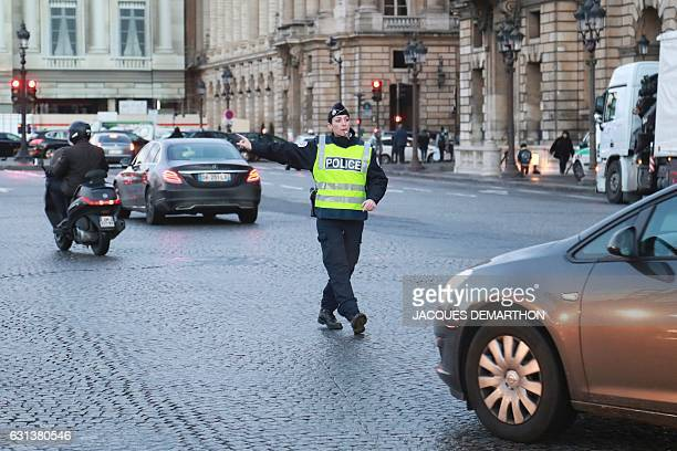 A French policeman controls drivers on January 10 2017 as part of a Crit'air ecovignette control operation on the place de la Concorde in Paris In...