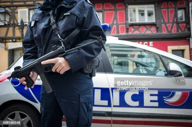 French policeman holds a weapon on November 21 2015 as he patrols at the Colmar Christmas market French lawmakers gave nearunanimous backing on...