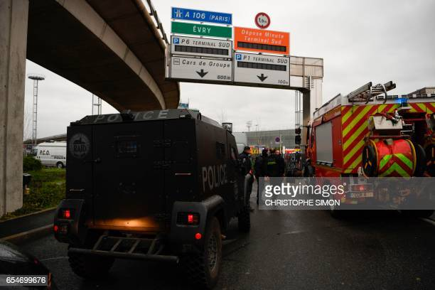 French policemen and firefighters secure the area at Paris' Orly airport on March 18 2017 following the shooting of a man by French security forces...