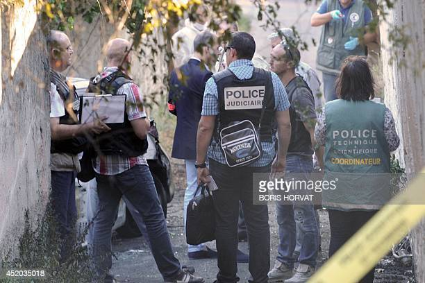 French policemen and forensic experts search evidence after a dead man was found in the trunk of a car on July 11 2014 in Marseille southern France...
