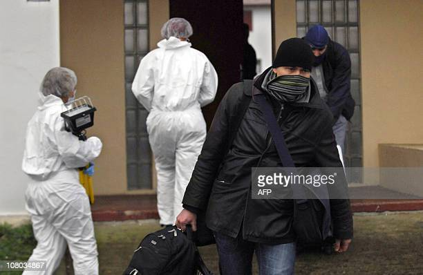 French policemen carry seized equipment as forensic experts enter the building where a presumed ETA member was arrested on January 11 2011 in Ciboure...
