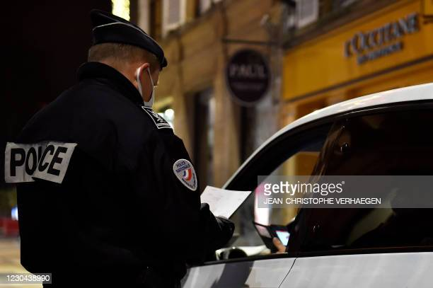French policemen check the attestation of a driver on January 5, 2021 in Metz, eastern France, as a new curfew is in effect at 6pm in 15 French...