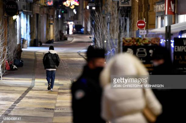 French policemen control people's attestation while a man walks in a deserted street on January 5, 2021 in Metz, eastern France, as a new curfew is...