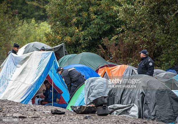 French policemen escorted by riot police count migrants on October 20 2015 in a makeshift camp in GrandeSynthe where 500 to 700 people most seeking...