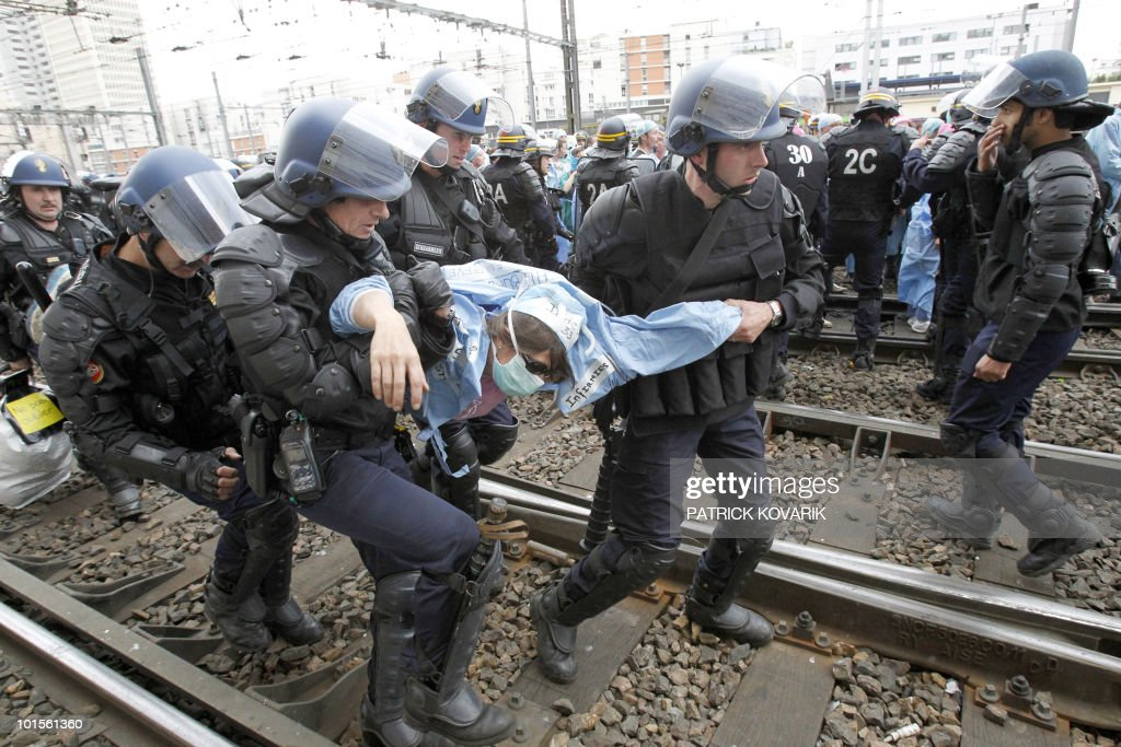 French policemen evacuate a woman during a demonstration of French anaesthetist nurses as they stand on tracks near the Montparnasse train station on May 18, 2010 in Paris, blocking the speed train (TGV) traffic, to protest against their work conditions.