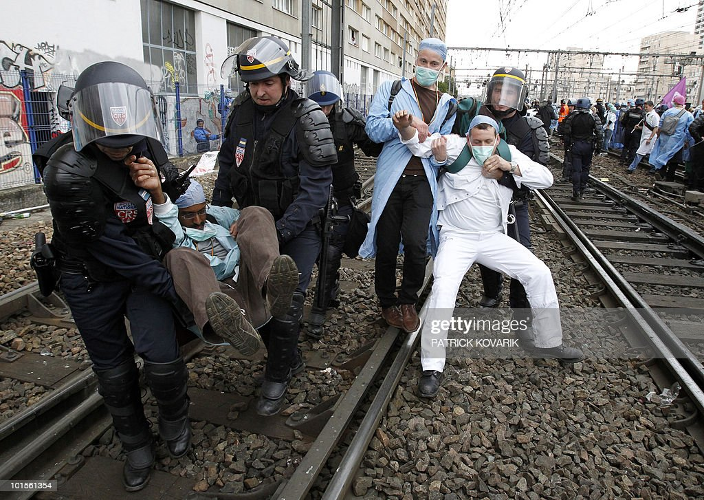 French policemen evacuate demonstrators during a rally of French anaesthetist nurses as they stand on tracks near the Montparnasse train station on May 18, 2010 in Paris, blocking the speed train (TGV) traffic, to protest against their work conditions.