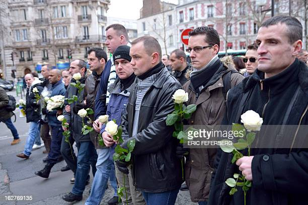 French policemen hold white roses as they take part in a silent march on February 26 2013 in Paris in the memory of two of their colleagues killed in...