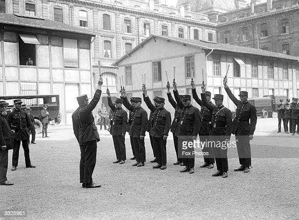 French policemen holding their batons above their heads during training in Paris