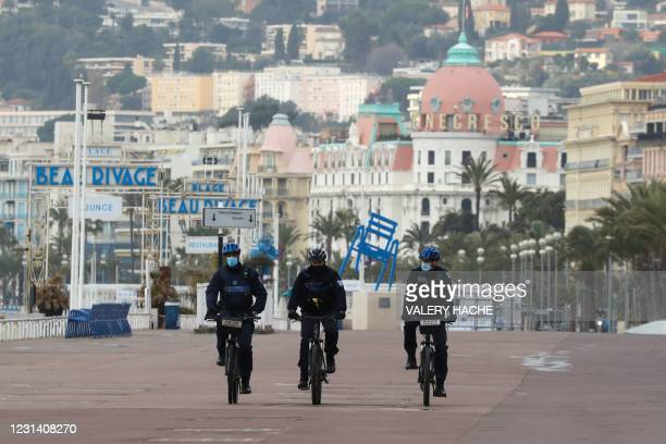"""French policemen on bikes patrol on the """"Promenade des anglais"""" of the French riviera city of Nice during the first weekend lockdown put in place by..."""