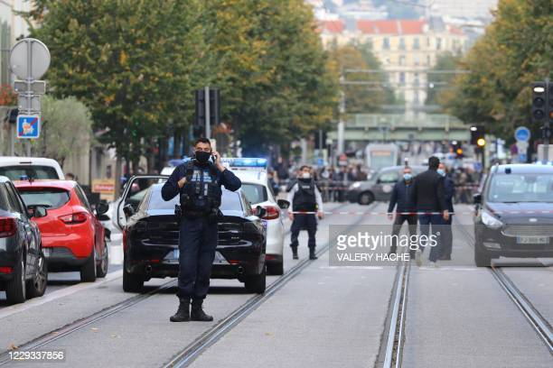 French policemen stand guard a street after a knife attack in Nice on October 29, 2020. - A man wielding a knife outside a church in the southern...