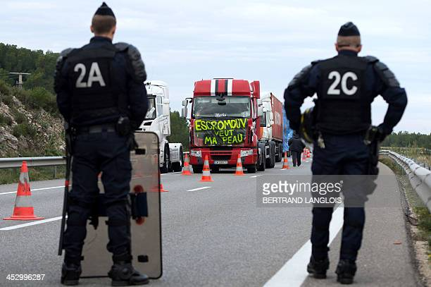 French policemen stand guard as drivers of heavy goods vehicles demonstrating against the ecotax block a section of highway A55 in...