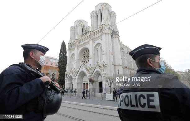 French policemen stand guard the site of a knife attack at the Basilica of Notre-Dame de Nice in Nice on October 29 as forensics officers prepare to...