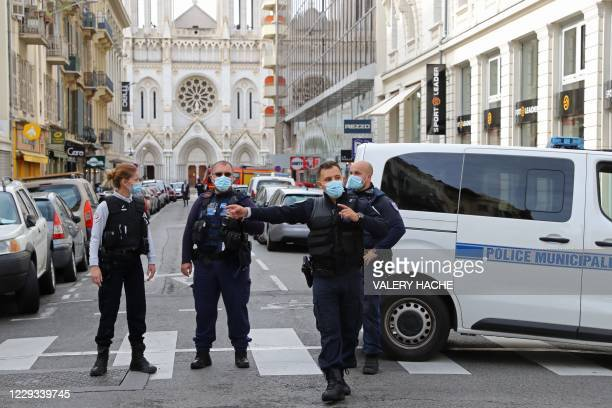 French policemen stand guard the street leading to the Basilica of Notre-Dame de Nice after a knife attack in Nice on October 29, 2020. - France's...