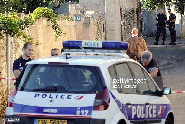 French policemen stand near an area where a dead man was found in the trunk of a car on July 11 2014 in Marseille southern France According to the...