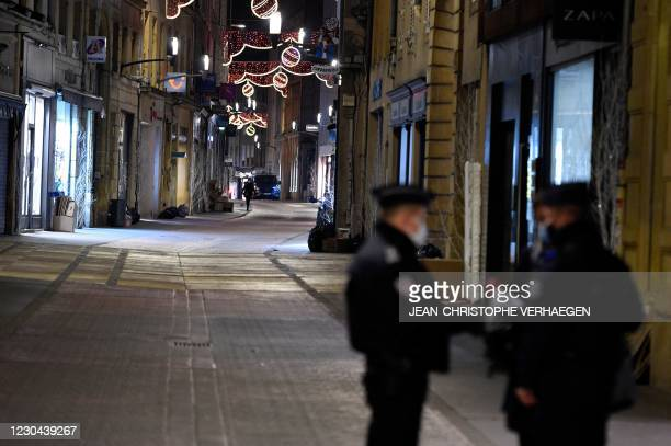 French policemen stand on a deserted street on January 5, 2021 in Metz, eastern France, as a new curfew is in effect at 6pm in 15 French departments...