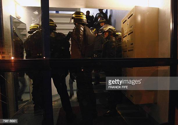 French policemen take position in the hall of a buiding on February 18 during a major predawn operation in and around VilliersleBel a northern Paris...