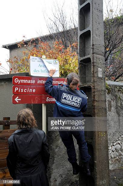 """French policewoman removes a sticker that covered up a road sign to rename it """"Avenue of the infidels"""", as part of a protest of the Bloc Identitaire..."""