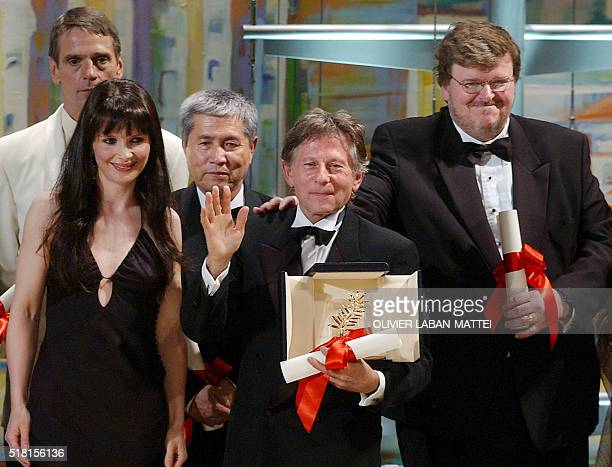 French Polish born director Roman Polanski waves to spectators surrounded by French actress Juliette Binoche the 55th Cannes film festival prize...