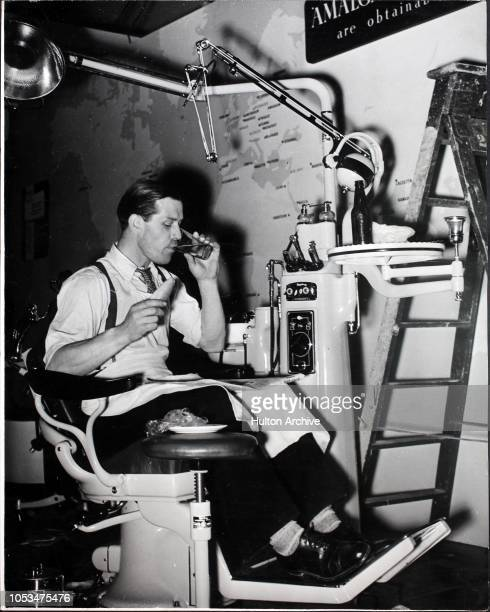 French polisher Mr W Osborne from London N16 having an interlude for lunch in a dentist's chair while arranging the exhibits at the Royal Festival...