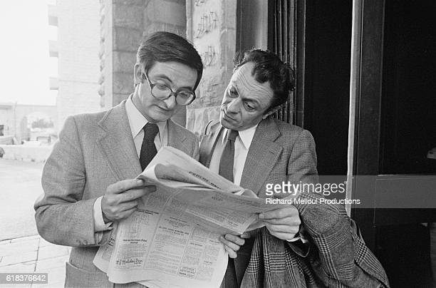 French political economist Jacques Attali and politician Michel Rocard read a newspaper with great interest