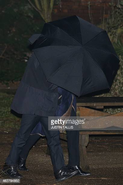 French politician and president of the Front National Marine Le Pen shelters under an umbrella as she walks through a quadrangle at the Oxford Union...