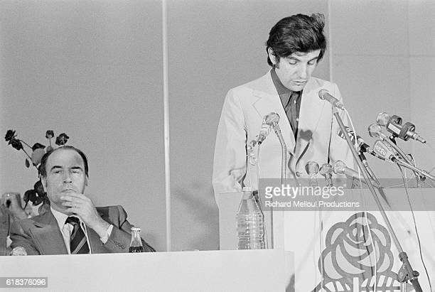 French politician JeanPierre Chevenement gives a speech during the 1974 Socialist Party national meeting as party leader Francois Mitterrand listens...