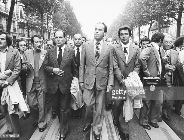 President Francois Mitterand Communist Party Leader Georges Marchais and Trade Unionist Georges Seguy leading a large group along a French street...