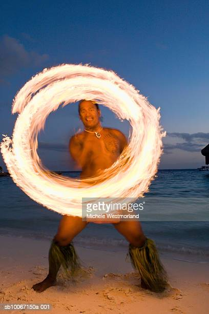 French Polynesia, Bora Bora, Bora Bora Nui resort, Traditional Tahitian fire dancer performing at dusk (blurred motion)