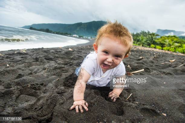 french polynesia, taharuu beach, baby girl playing in black sand - black ginger baby stock photos and pictures