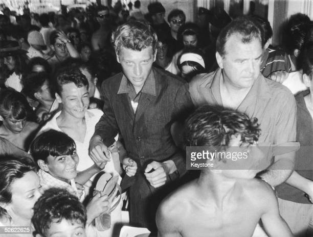 French pop star Johnny Hallyday and manager Johnny Starck are mobbed by fans after local authorities in Cannes banned a Hallyday concert fearing 'too...