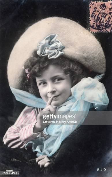 French postcard dated circa 1900 showing a young girl gesturing silence or perhaps sharing a secret