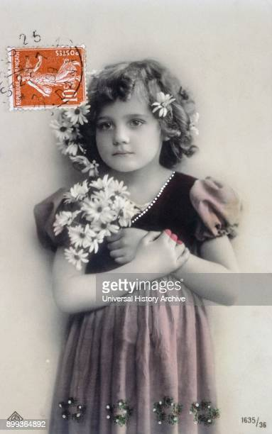 French postcard dated circa 1900 showing a young girl with flowers