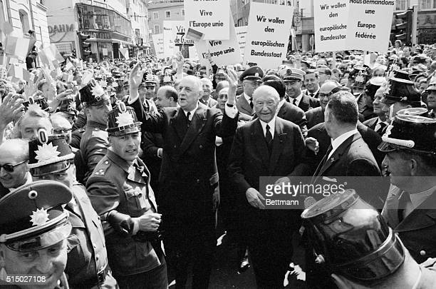 French Premier Charles de Gaulle acknowledges a supportive West German crowd as he passes through with West German Chancellor Konrad Adenauer in Bonn...