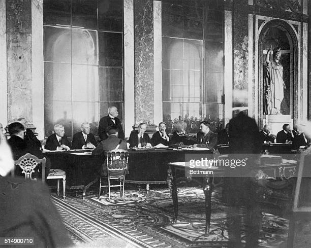 French Premier Georges Clemenceau rises to speak at the signing of the Treaty of Versailles in 1919. U.S. President Woodrow Wilson is seated to...